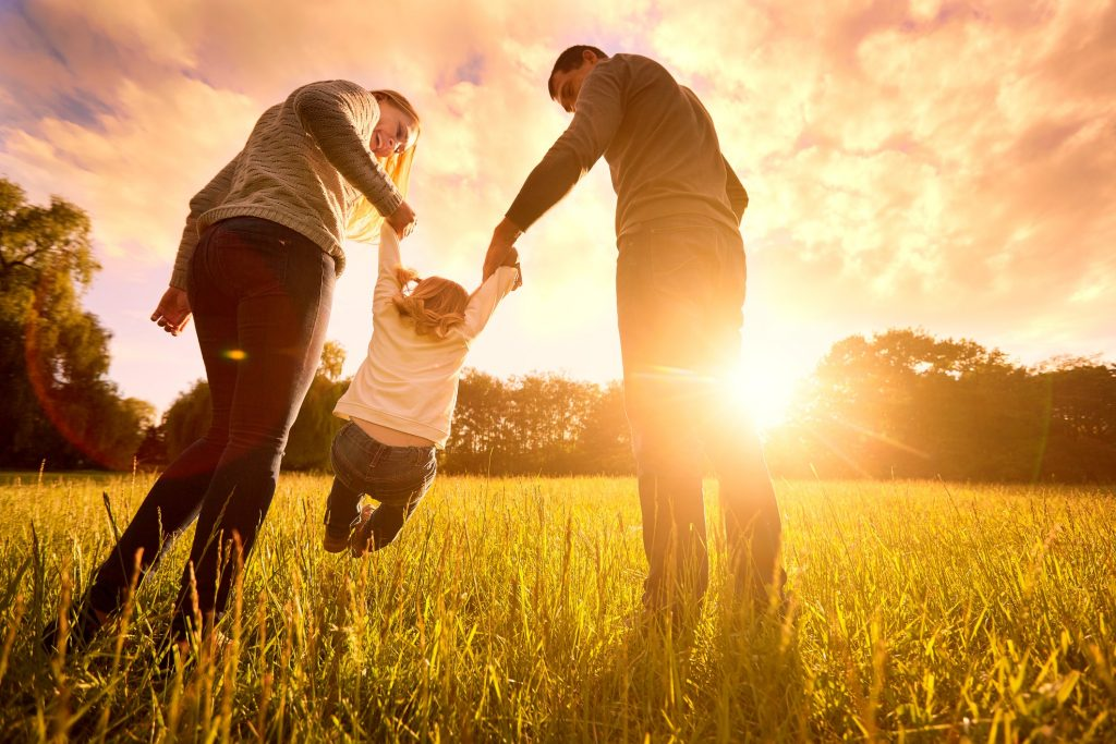 Family swinging daughter in grass during sunset